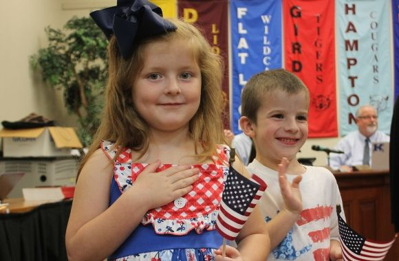 Student holds flag while reciting the Pledge