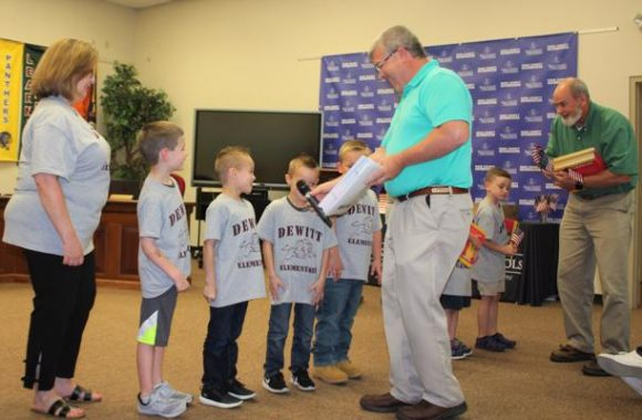 Board members are shown presenting certificates and books to Dewitt kindergarten students