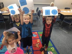 Students shown with a paper with shapes during Play Learn Groups.