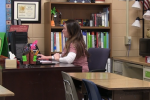 Teacher shown at desk with computer and webcam.