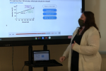 Teacher shown in front of Aver Board with math equation on screen.