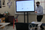 Social studies teacher shown looking at a Chromebook sitting in a seat representing online students.